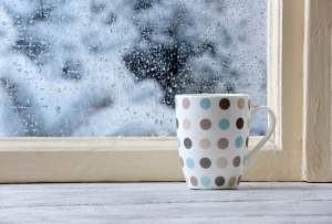 Cup of hot drink on windowsill on rain background